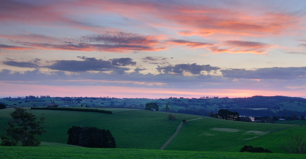Photo of sunset over rolling green hills