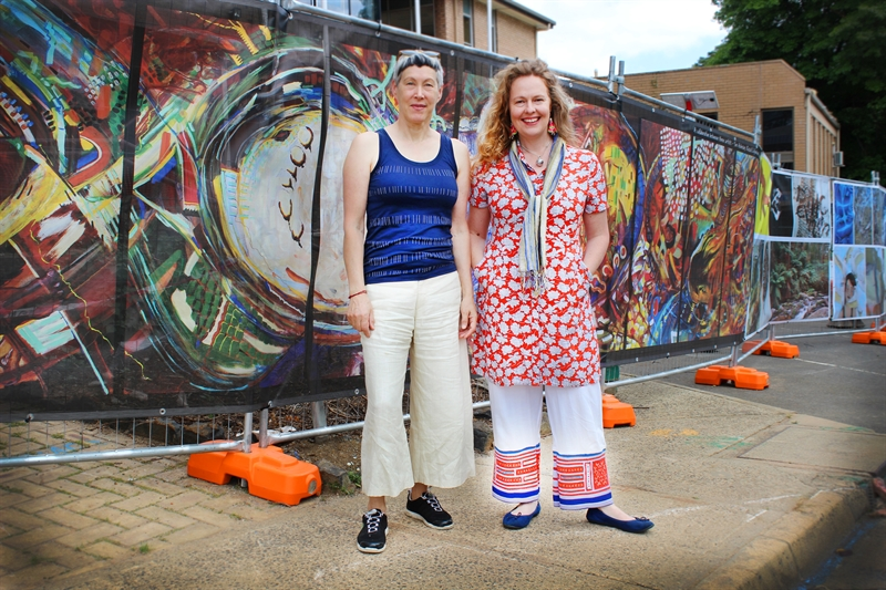 Artists Sue Acheson and Bec Van Dyk stand in front of pop up display, wide shot