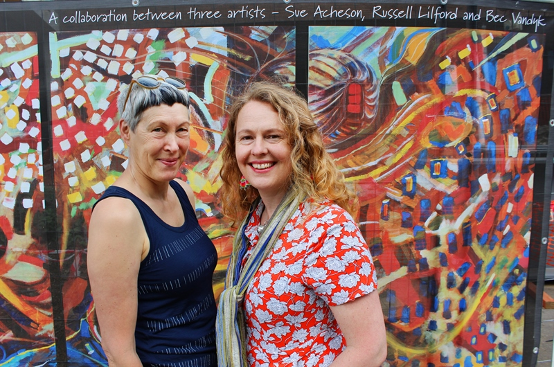Artists Sue Acheson and Bec Van Dyk stand in front of pop up display, close-up shot
