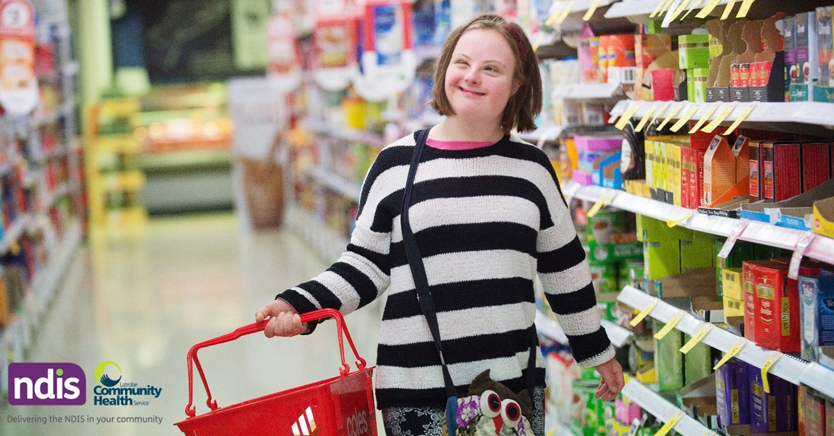 Young woman with disability carrying shopping basket in supermarket